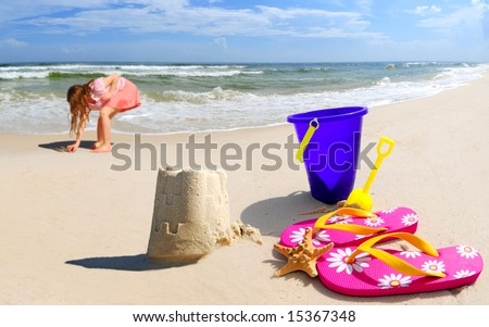 Girl collecting shells by pretty sand castle on seashore by beach accessories - stock photo