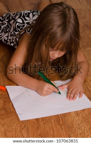 Girl coloring on the kitchen floor - stock photo