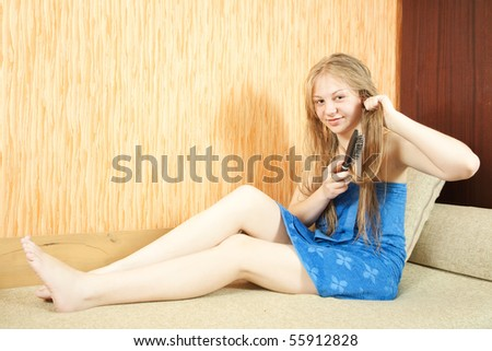 Girl combing her long hair in home interior - stock photo
