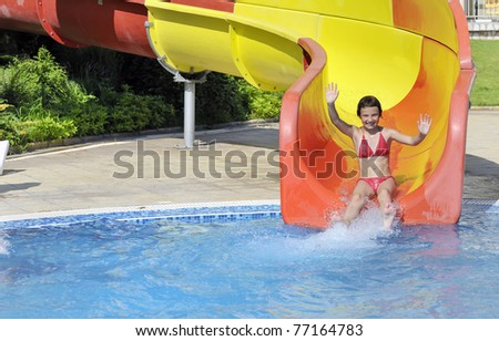 girl comes down the slide into the pool - stock photo