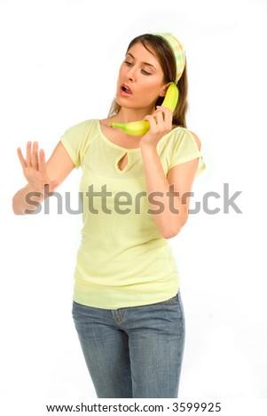 Girl conduct conversation using banana as phone - stock photo