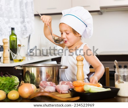 girl cooking soup  with ladle at home   - stock photo