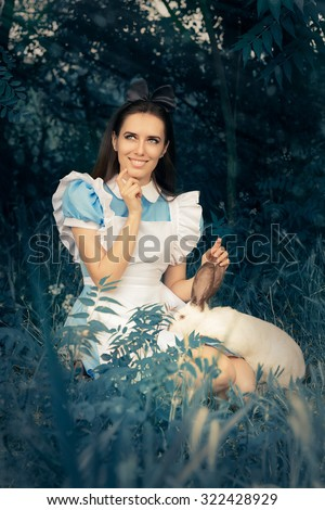 Girl Costumed as Alice in Wonderland with The White Rabbit - Portrait of a smiling girl in a blue costume holding a white bunny  - stock photo