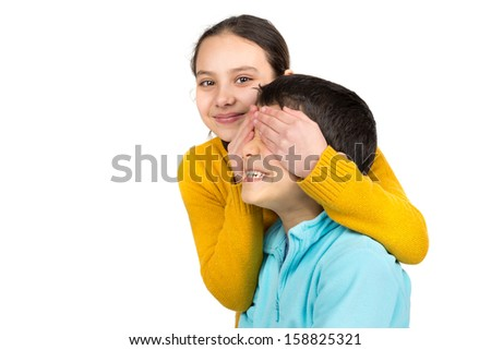 Girl covering boy's eyes isolated in white