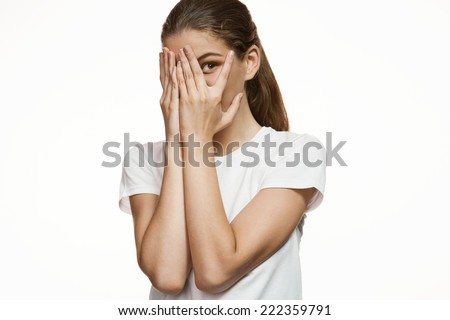 Girl covering face with hands, hiding face with hands / Gorgeous girl in plain white T-shirt. Mixed race Latina Caucasian young woman gesticulating - isolated on white background.  - stock photo