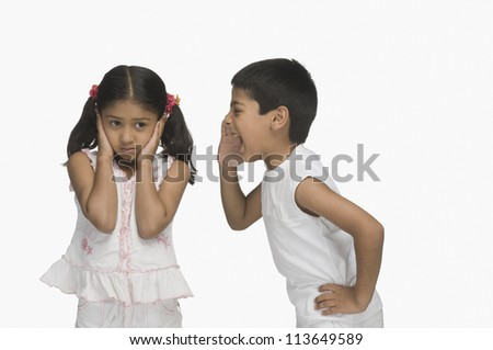 Girl covering her ears while her brother shouting - stock photo