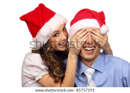 Girl covering the eyes of her boyfriend. Isolated over white background - stock photo