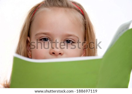 Girl covers her face with book at - stock photo