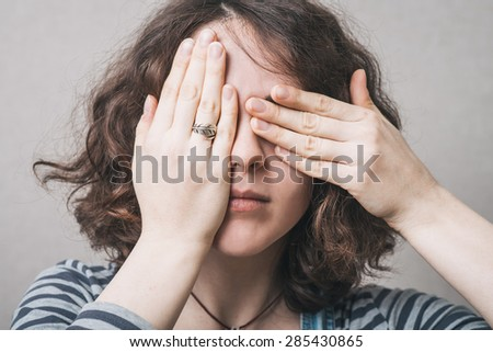 girl covers her face with her hands - stock photo
