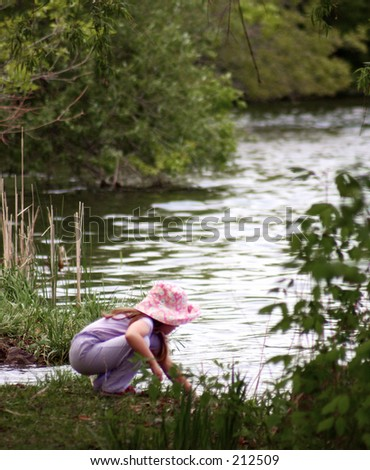 Girl crouching by river - stock photo