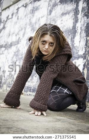 Girl crouching desperate fear in urban street - stock photo