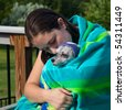Girl cuddling a wet dog in a towel after a swim - stock photo