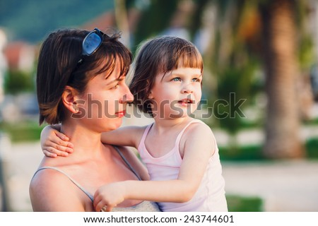 Girl cuddling mother. Little cute girl in mother's arms during summer holiday walk - selective focus (girl's eyes perfectly sharp - mother face is slightly out of focus) -very shallow depth of field - stock photo