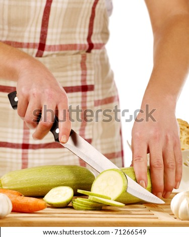 Girl cutting gourd with the knife, on a wooden plate - stock photo