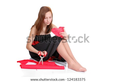 girl cutting valentine heart out of red paper with scissors over white background