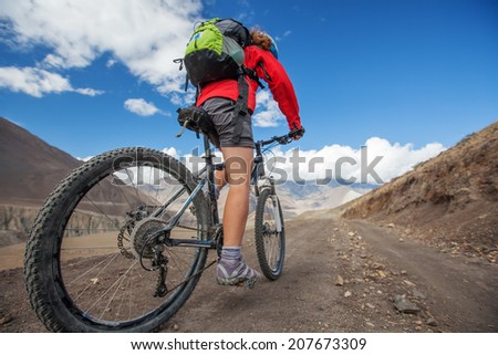 Girl cycling at the road in Himalaya