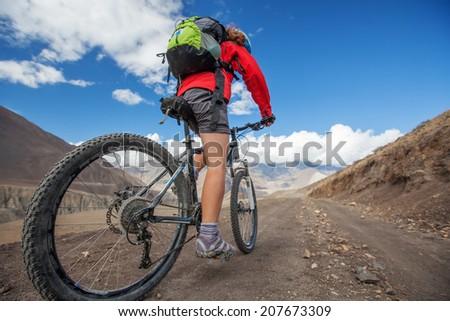 Girl cycling at the road in Himalaya - stock photo