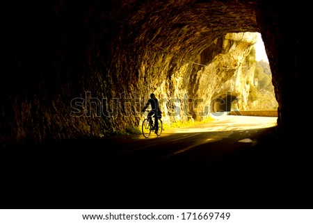girl cycling through tunnel - stock photo