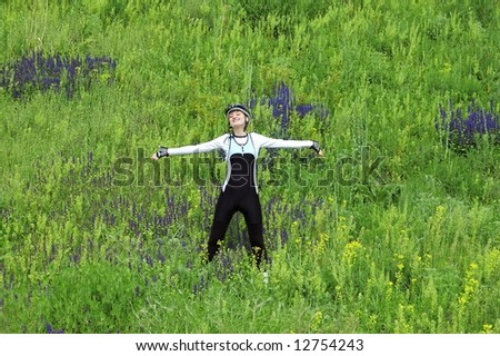 Girl cyclist in sportive clothes and helmet is standing on a green field - stock photo