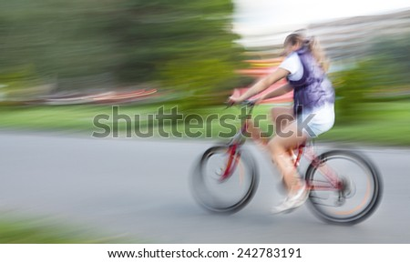 Girl cyclist in traffic on the city roadway. Intentional motion blur - stock photo