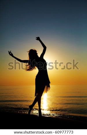 Girl dances on the beach at sunset. Natural light and dark. Artistic colors added. Vertical photo