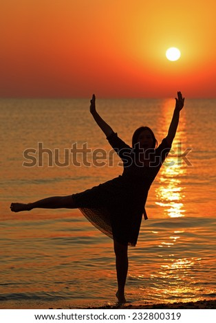 Girl dancing on the background of sunrise over the sea. Shallow depth of field. - stock photo