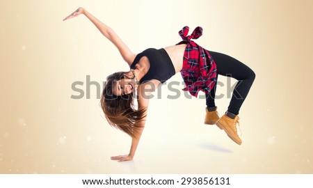 Girl dancing street dance over ocher background - stock photo