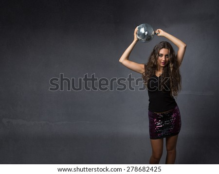 girl dancing with disco ball on hand, dark background - stock photo