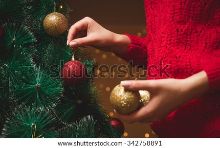 Girl decorates a Christmas tree - stock photo
