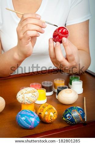 Girl decorates Easter eggs - stock photo
