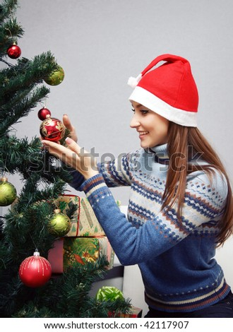 Girl decorating Christmas tree at home