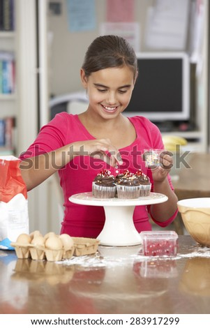 Girl Decorating Homemade Cupcakes In Kitchen - stock photo
