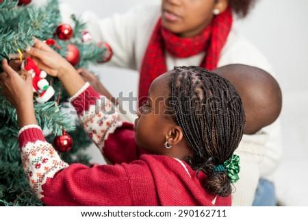 Girl decorating the christmas tree - stock photo