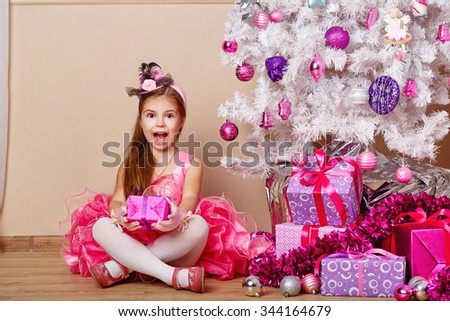Girl delighted with gift. Child wearing a dress and sitting next to the Christmas tree. New Year. Holiday and fun. Merry Christmas. Human emotions. 2017 - stock photo