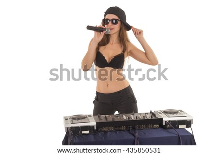 Girl DJ in the black bra is singing to the microphone and touching her cap - stock photo