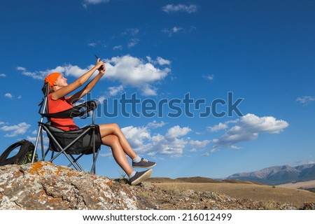 Girl doing a self-portrait on a smartphone, sitting in a folding camping chair  - stock photo