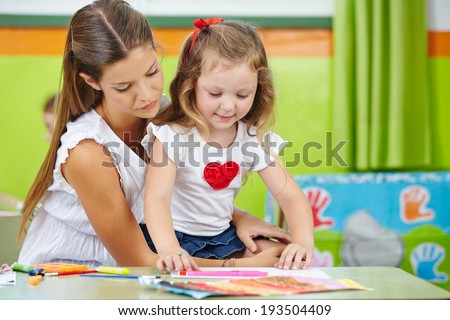 Girl doing arts and crafts with mother in nursery room - stock photo