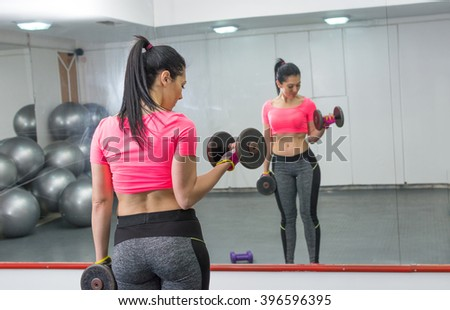 Girl doing biceps workout in front of a mirror