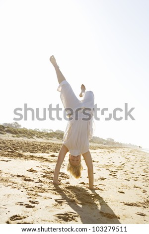 Girl doing cartwheels on a beach with golden sunshine. - stock photo