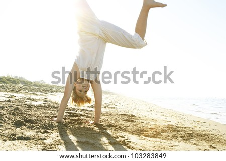 Girl doing cartwheels on the beach with the sun filtering through her legs. - stock photo