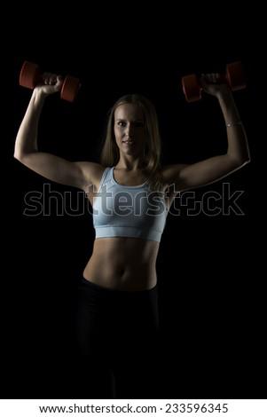 girl doing exercise on black background - stock photo
