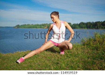 girl doing exercise on the bank of river - stock photo