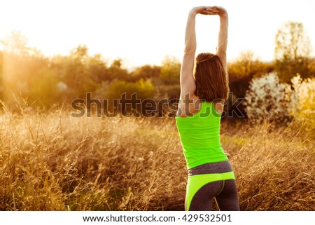Girl doing exercises at dawn - stock photo