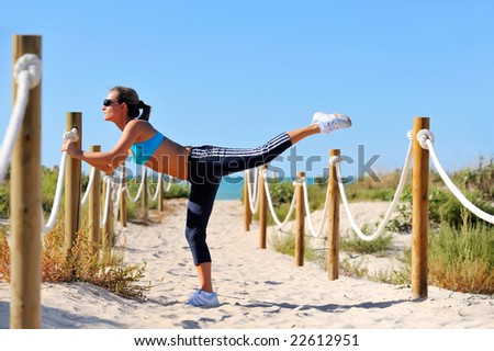 girl doing exercises on the beach - stock photo