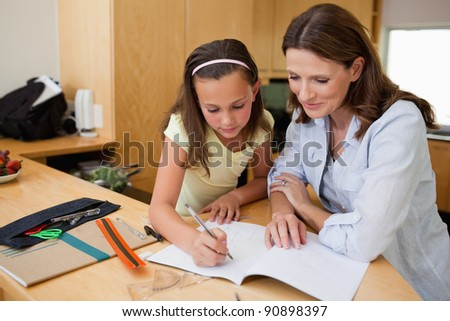 Girl doing homework together with her mother - stock photo