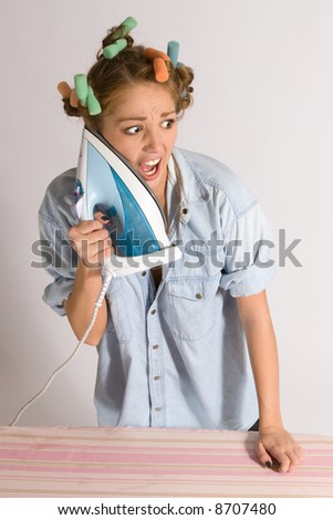 Girl doing housework with hair curlers. - stock photo