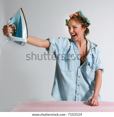 Girl doing housework with hair curlers. Holding an iron towards her face and standing in front of an ironing board with laughing expression. - stock photo