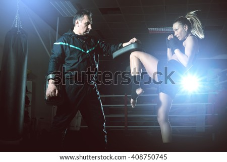 Girl doing knee kick exercise during kickboxing training with personal trainer - stock photo