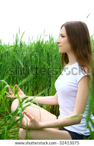 Girl doing meditation on meadow - stock photo