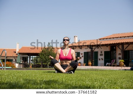 Girl doing meditation on meadow against a house and the sky